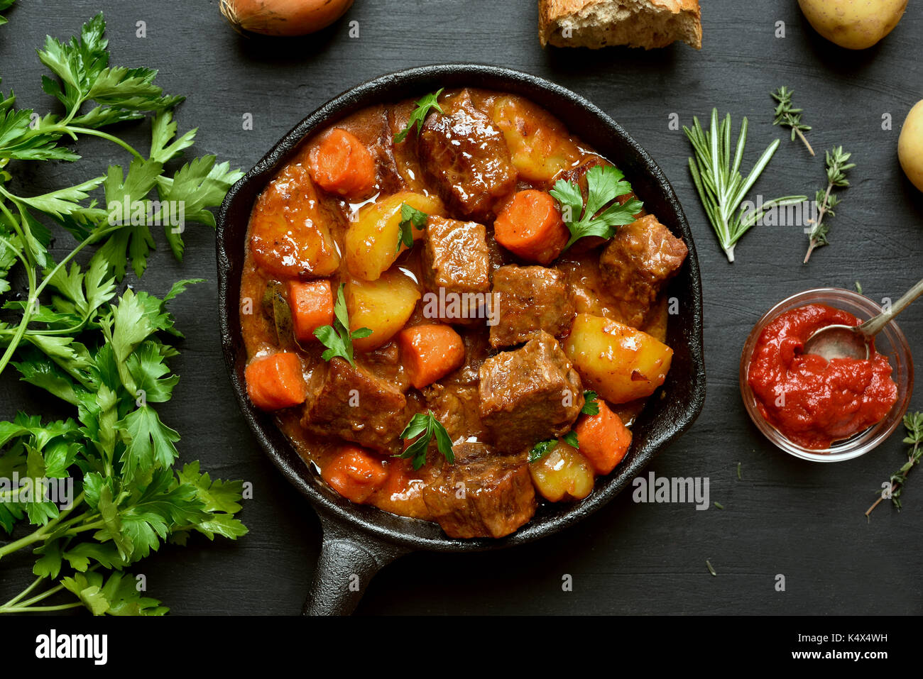 Stewed beef and vegetables in frying pan, top view - Stock Image