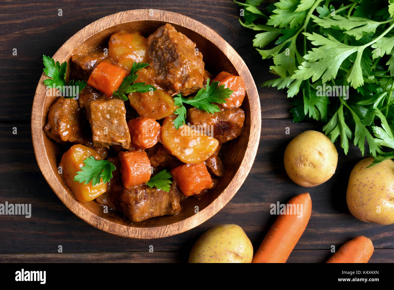Meat stew with vegetables in bowl on wooden background, top view - Stock Image