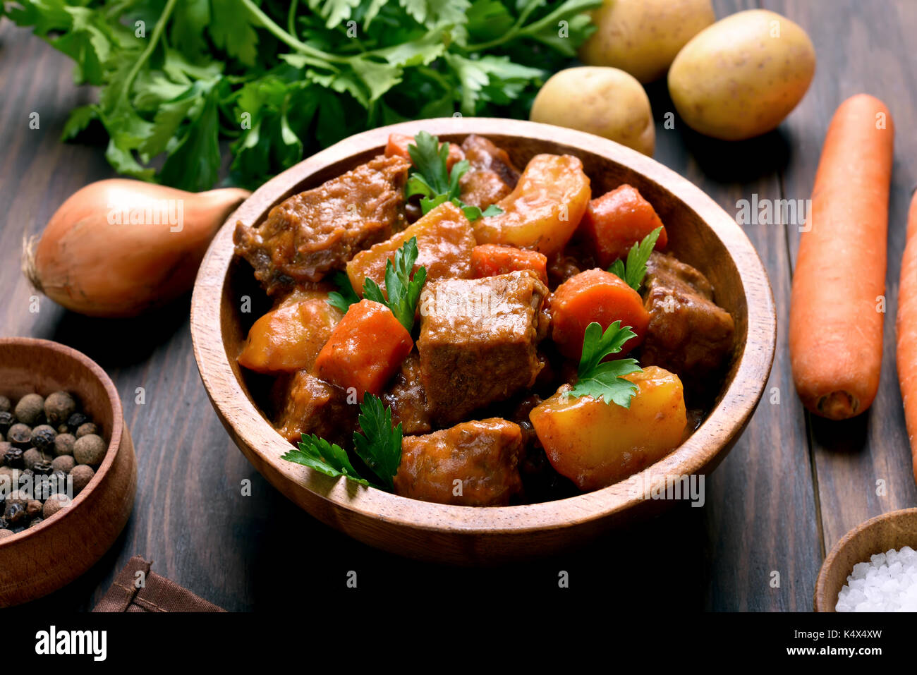 Dish for dinner. Meat stew with vegetables in wooden bowl - Stock Image