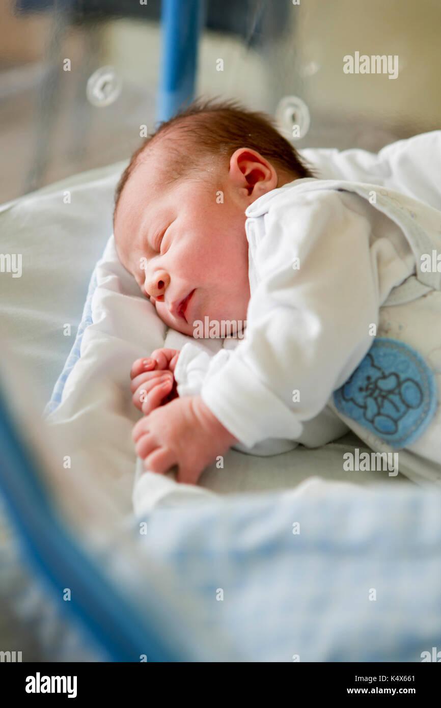 Beautiful newborn baby boy, laying in crib in prenatal hospital Stock Photo