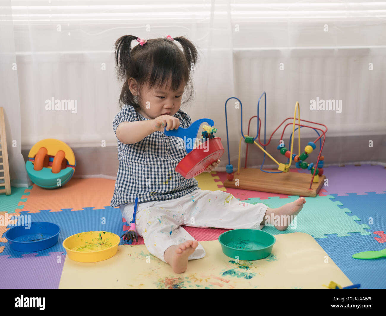 Baby girl play finger paints at home - Stock Image
