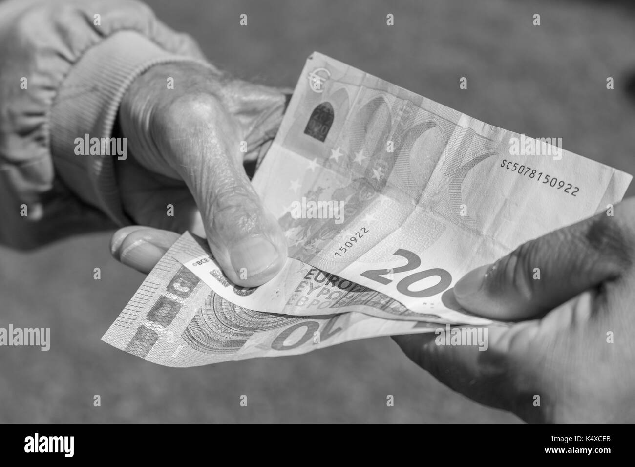 Senior man's hands holding Euro banknote.  pensioners concept. - Stock Image