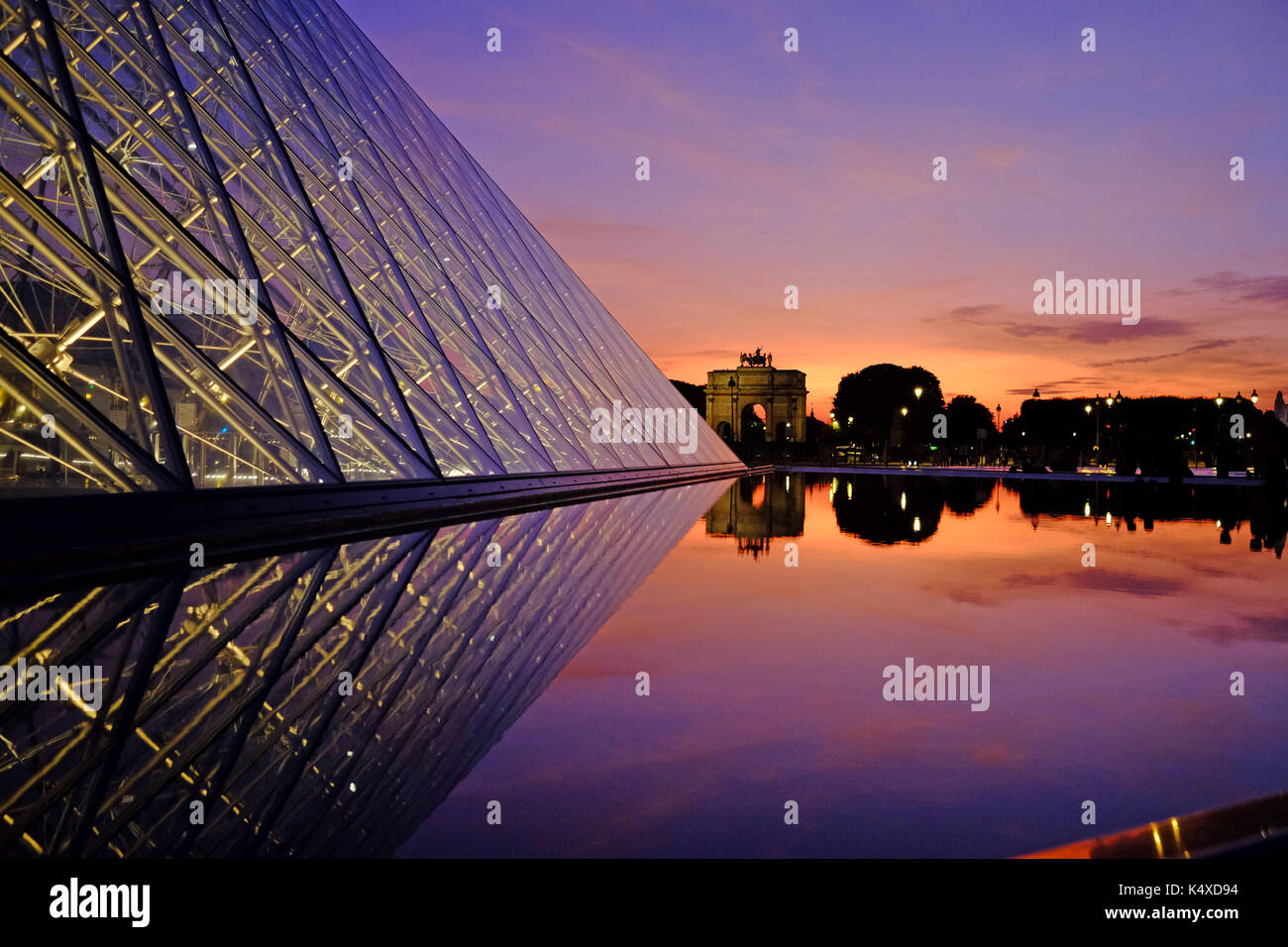 The Louvre in Paris at night as the sun sets - Stock Image