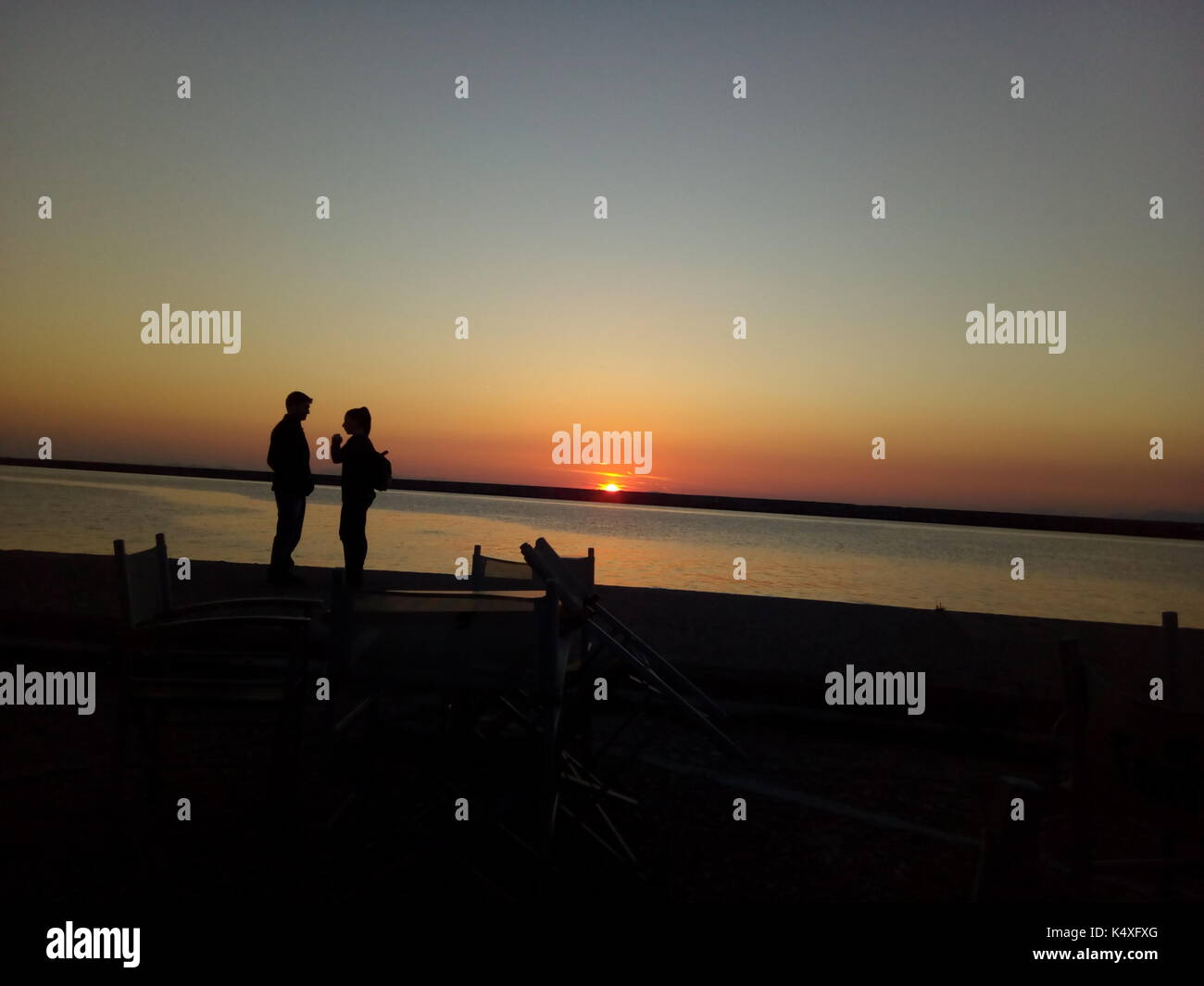 a couple sillouette talking at the sunset - Stock Image