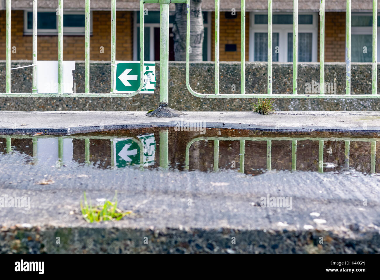 Broken green emergency exit sign and its reflection from a puddle for concept use - Stock Image