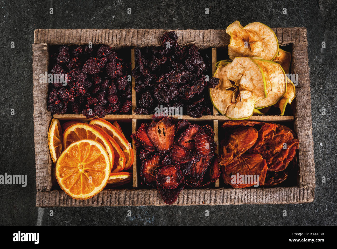 Homemade dried berries and fruits, harvest for the winter: apricots, apples, strawberries, raspberries, cherries, oranges. In old wooden box, on black - Stock Image