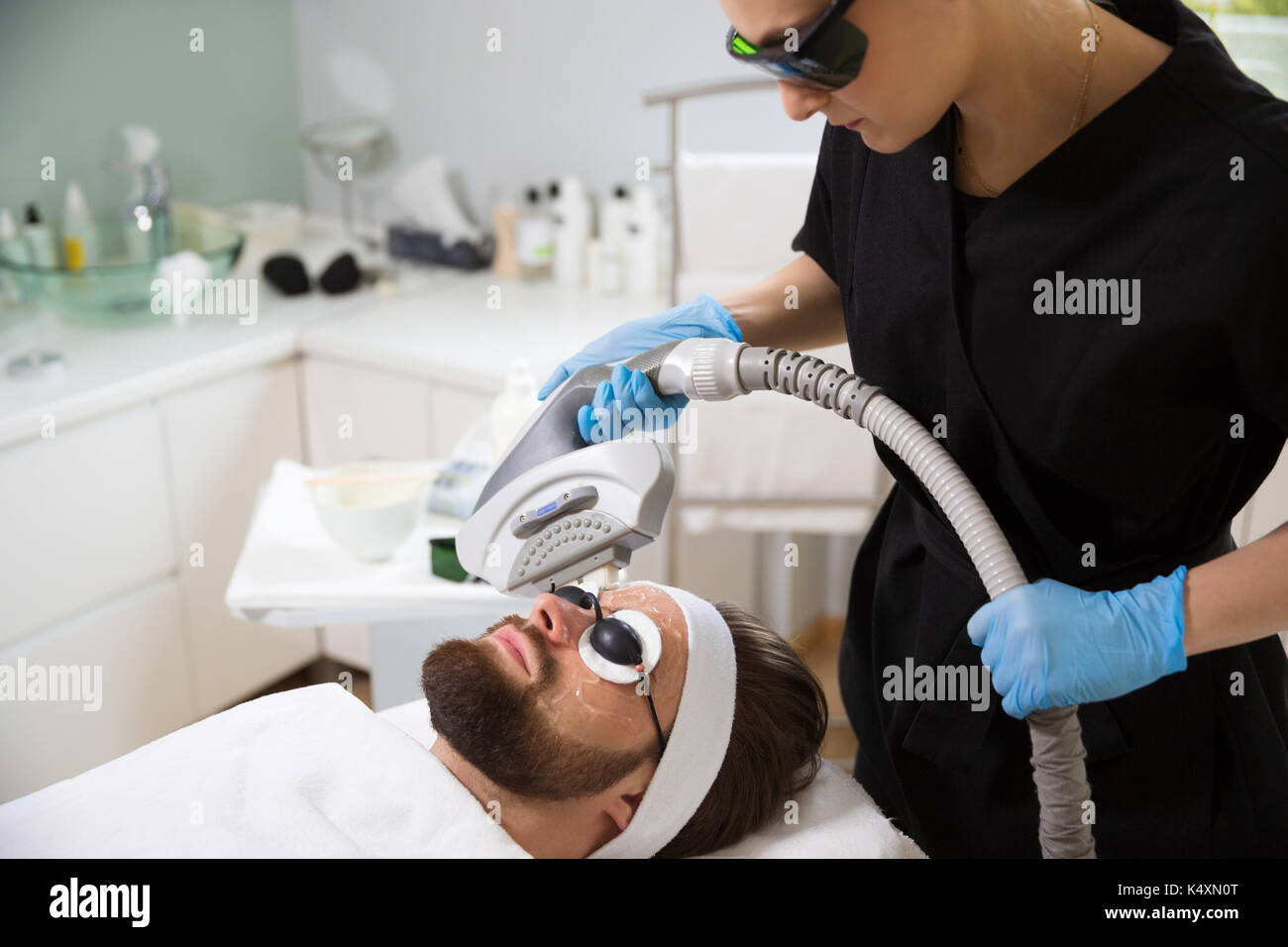 Man at beautician's during laser anti-aging therapy - Stock Image