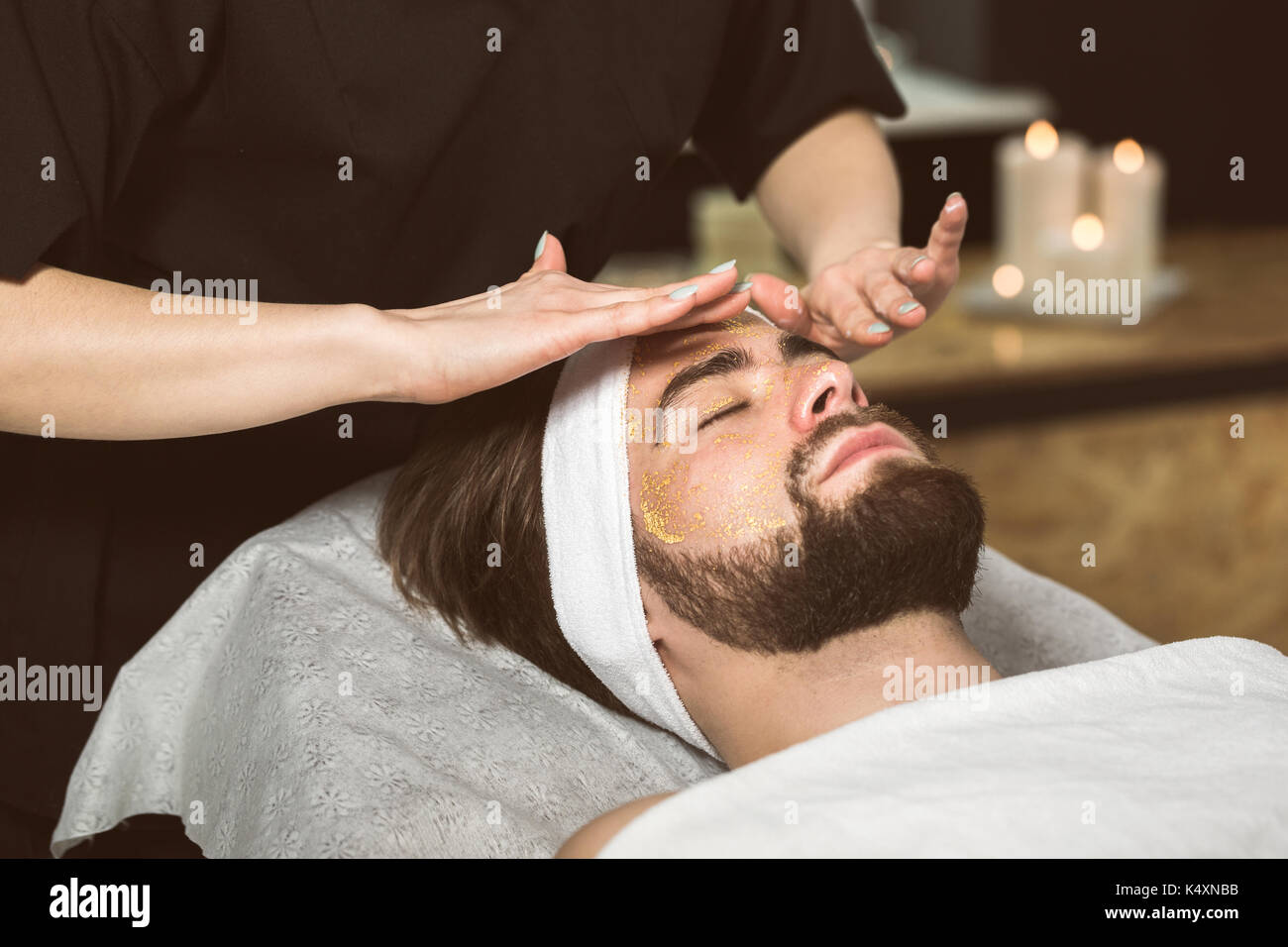 Man at beautician's during gold mask anti-aging therapy - Stock Image