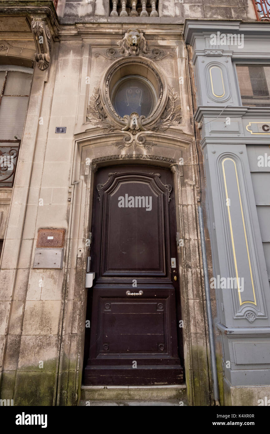Old brown door in an old building (Bayonne, France). - Stock Image