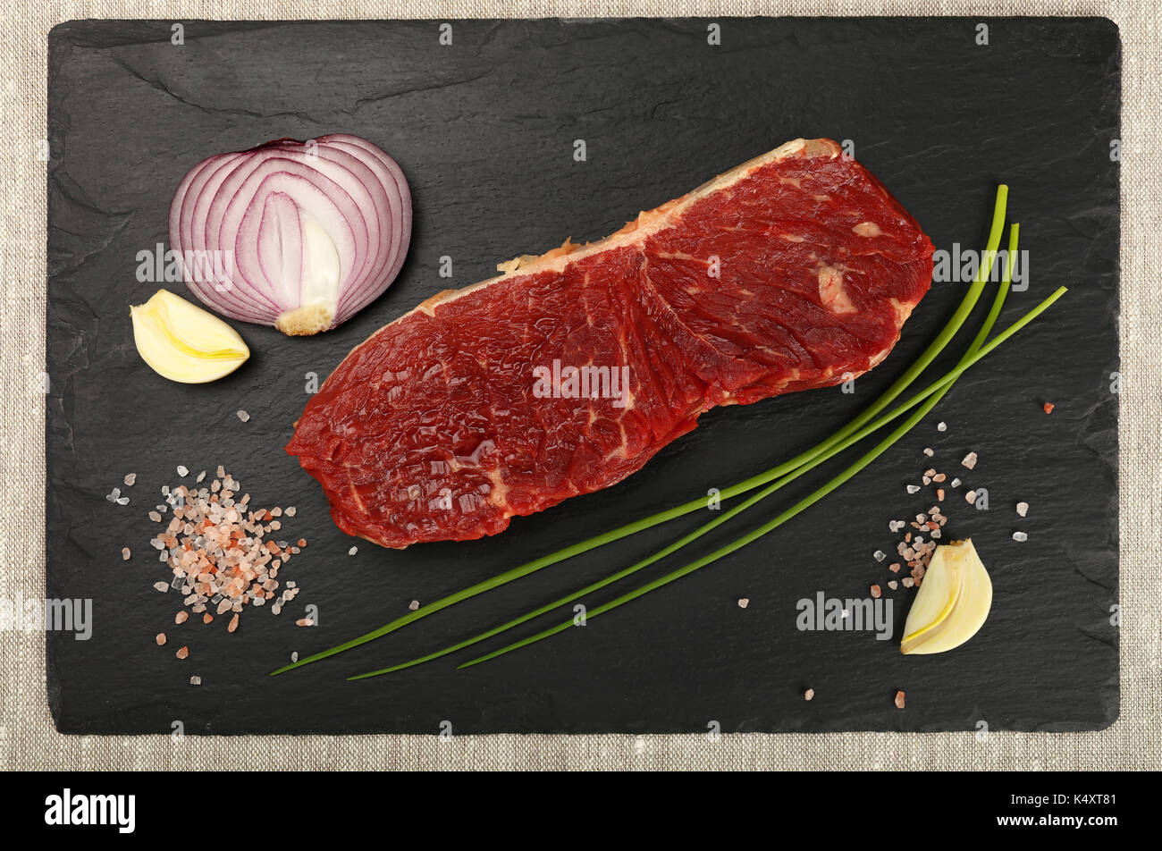 One raw beefsteak red meat cut, spices, peppercorn in wooden scoop, green spring chive, onion, garlic and Himalayan salt on black slate board, close u - Stock Image