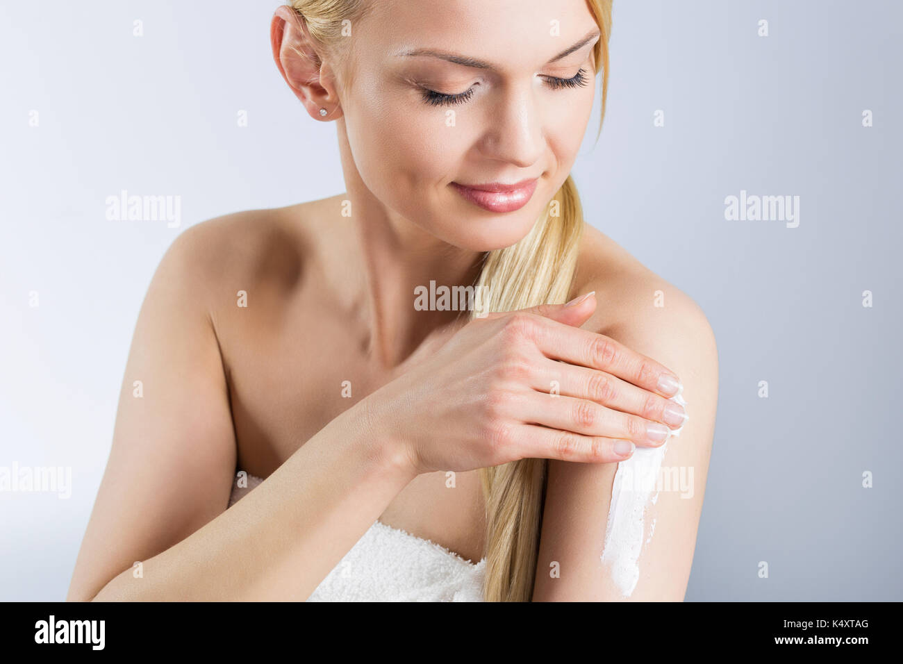 Portrait of beautiful young woman applying cream on arm - Stock Image