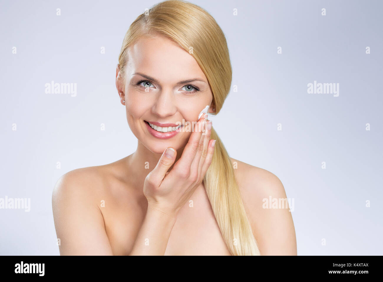 Front portrait of young pretty woman applying cream on face - Stock Image