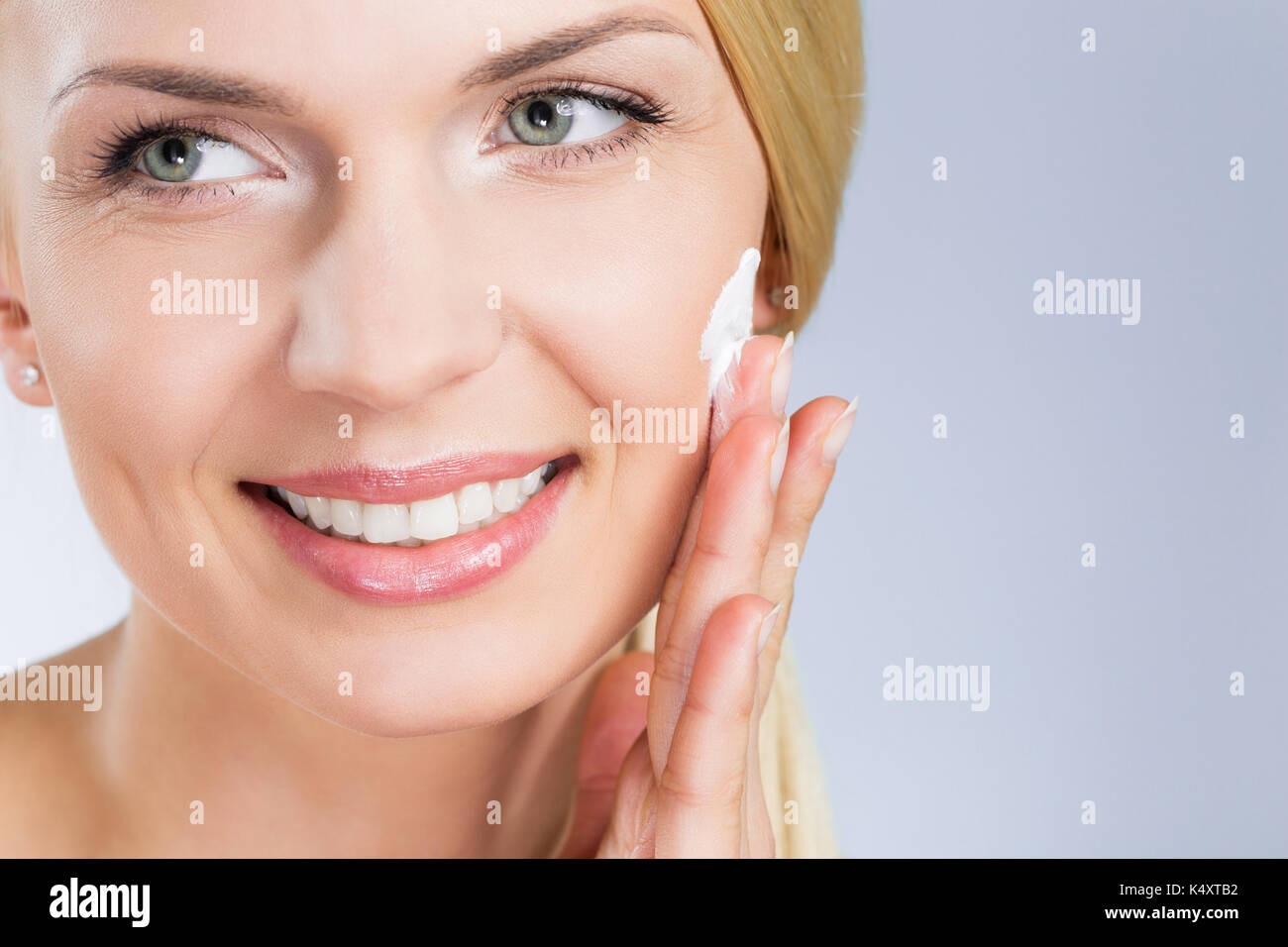 Close up portrait of happy woman applying cream on face looking away - Stock Image