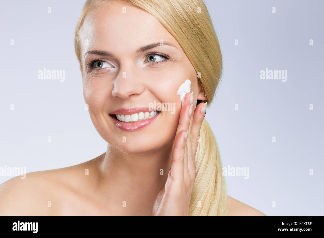 Close up portrait of young happy woman applying cream on face looking away - Stock Image