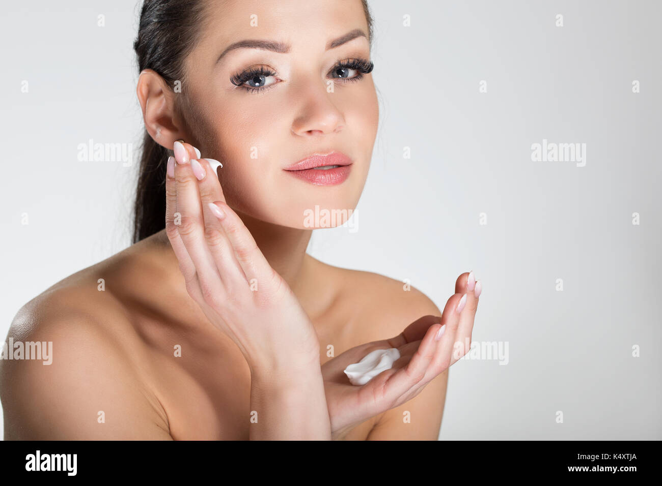 Portrait of pretty smiling woman applying cream on face - Stock Image