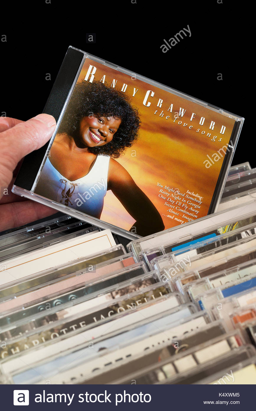 Love Songs, Randy Crawford CD being chosen from among rows of other CD's, Dorset, England - Stock Image