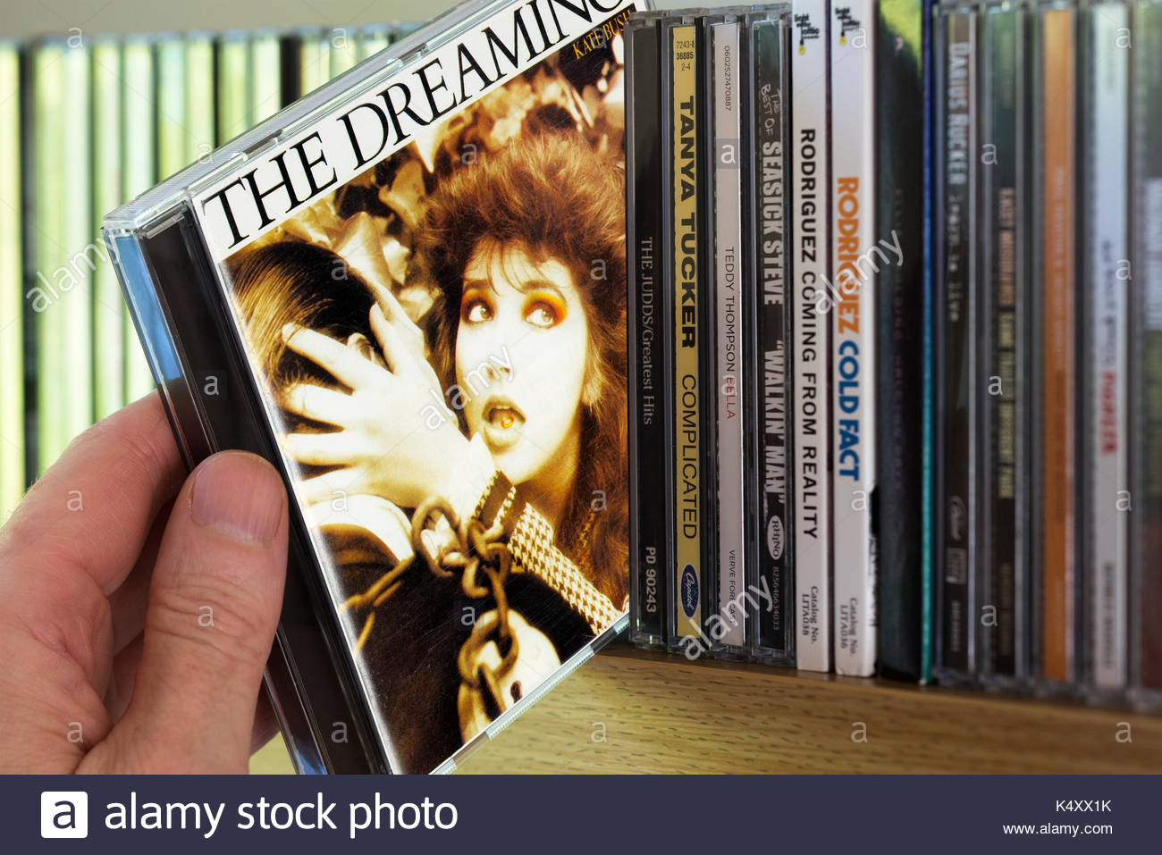 The Dreaming, Kate Bush CD being chosen from a shelf of other CD's, Dorset, England Stock Photo