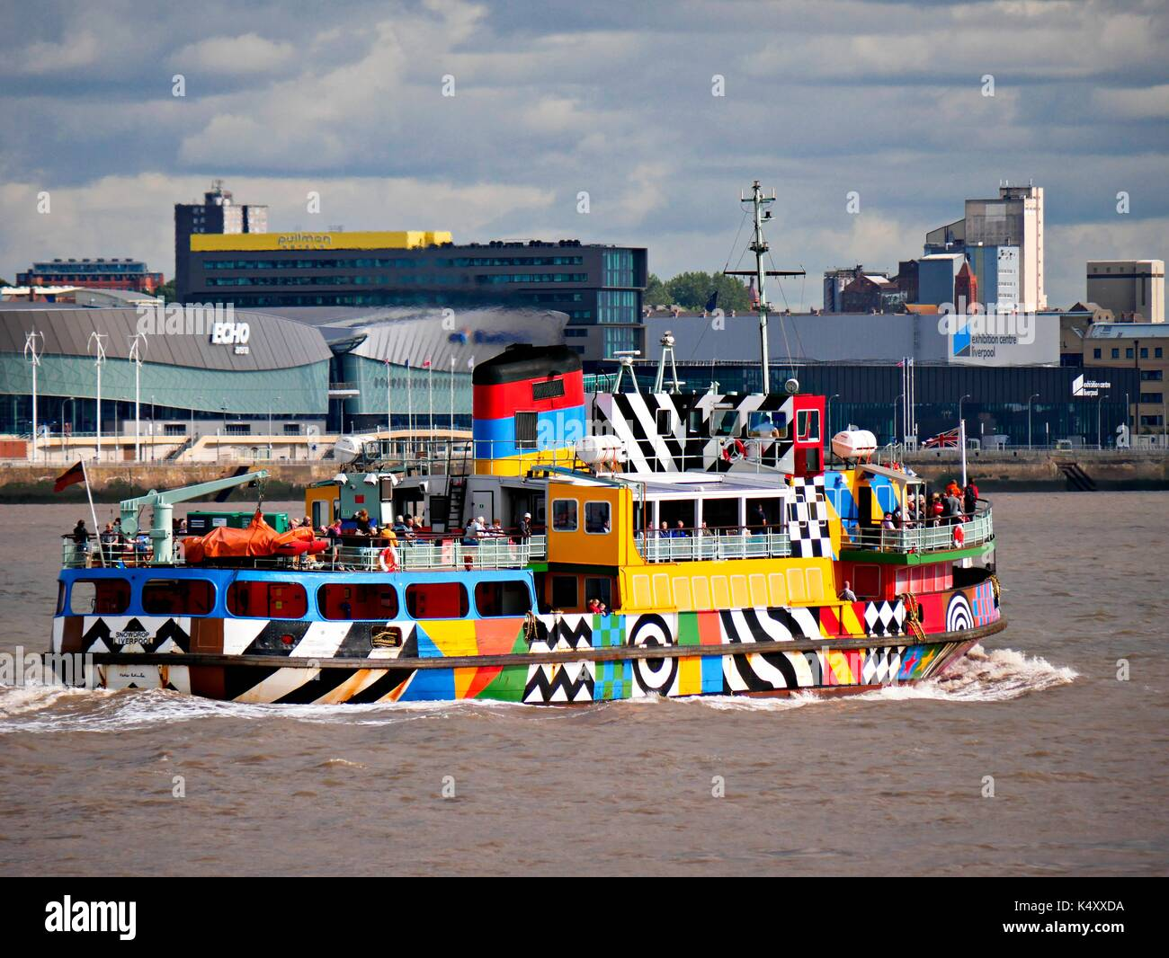 Mersey Ferry in dazzle livery against the backdrop of the Liverpool Arena and Exhibition Centre. - Stock Image