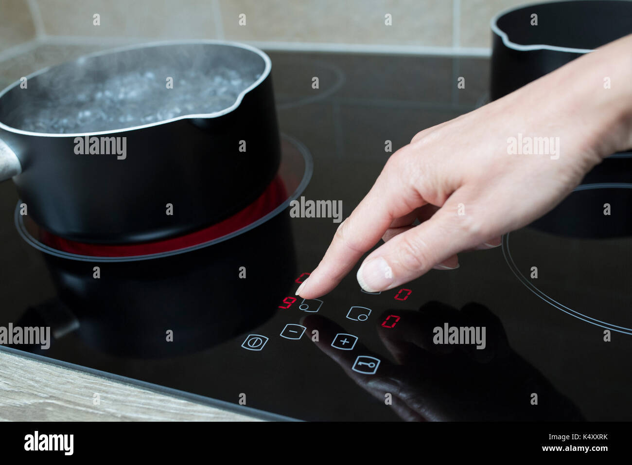 Close Up Of Woman Adjusting Temperature Of Halogen Hob In Kitchen - Stock Image