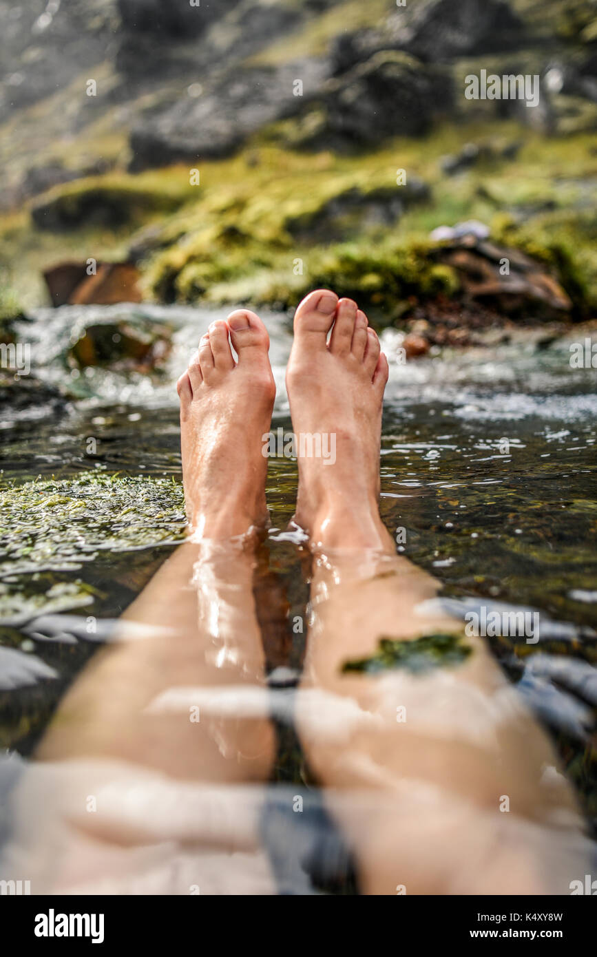 Woman bathing in a hot spring in Iceland, in the Landmannalaugar mountains, view of the feet. Stock Photo