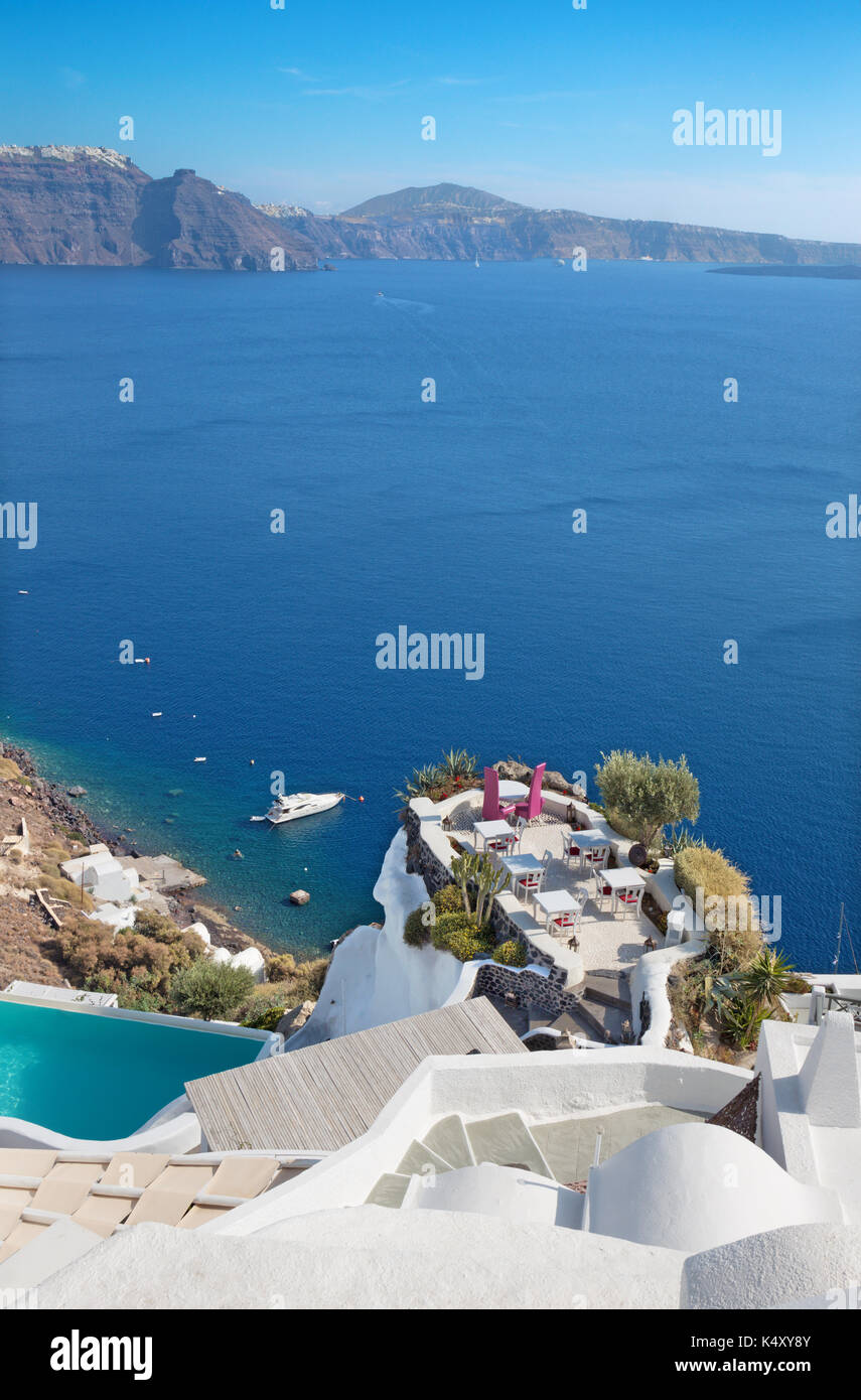 Santorini - The restaurant geared to wedding romantic diner in Oia (Ia) and the yacht under cliffs in the background. - Stock Image