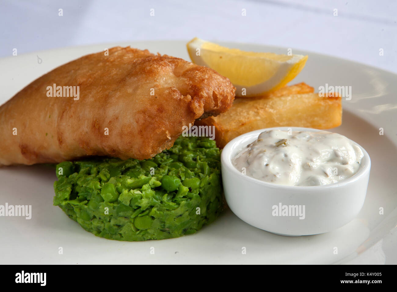 Battered fish and chips with mushy peas and tartar sauce on a plate - Stock Image