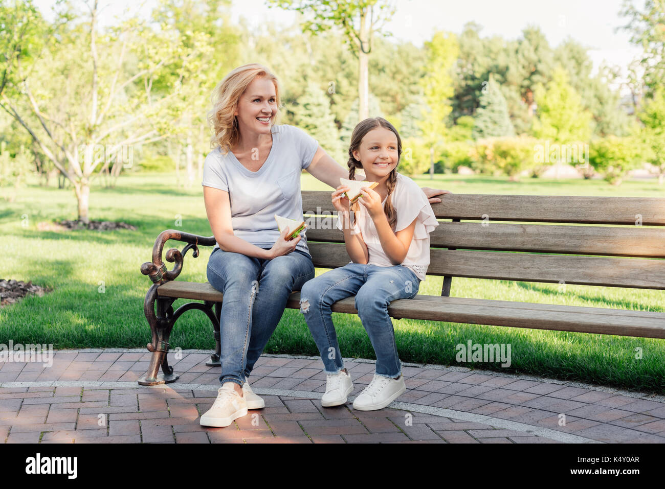 woman and granddaughter eating sandwiches - Stock Image