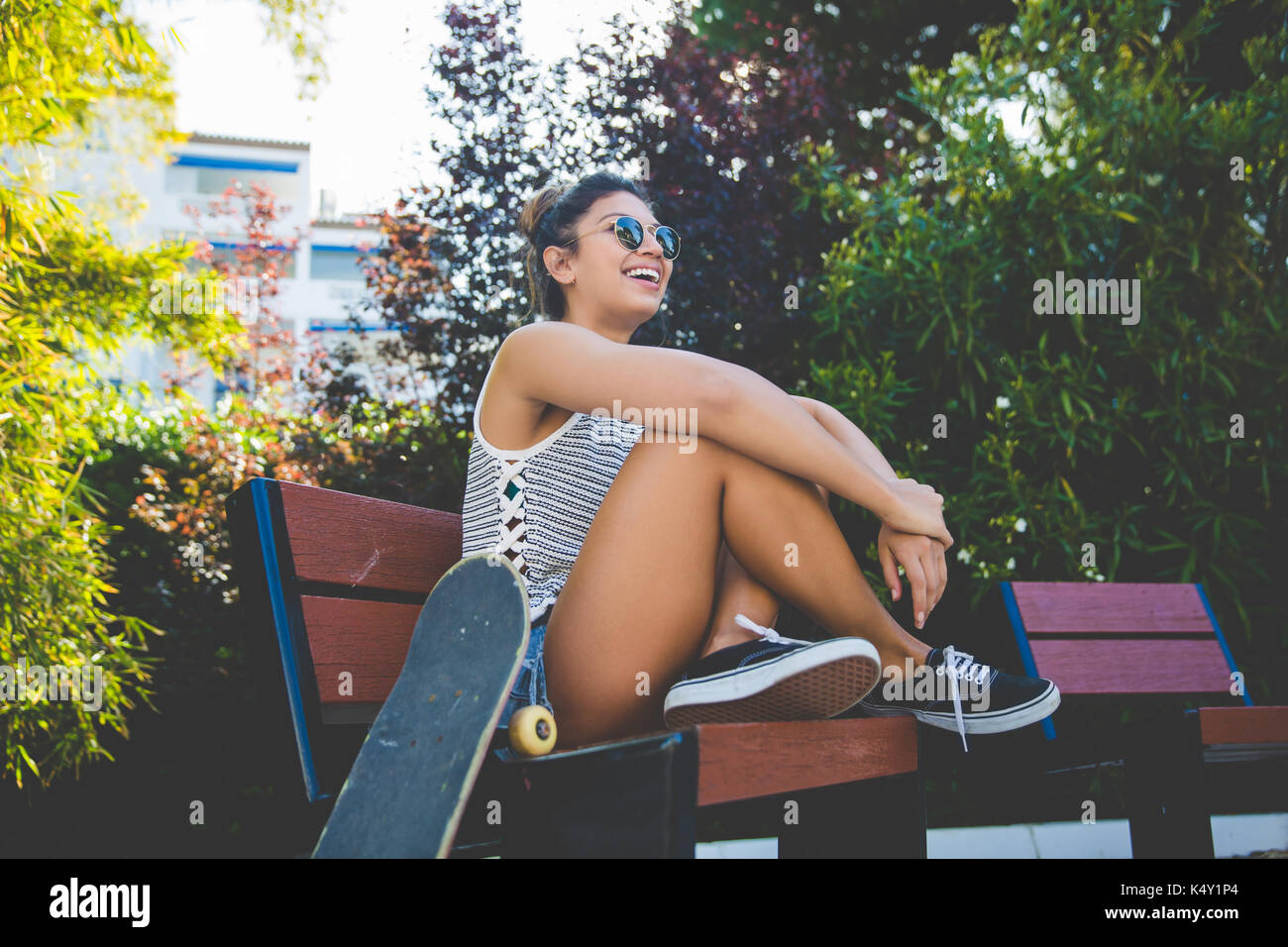 Portrait of young pretty woman sitting on beach with skateboard laughing - Stock Image