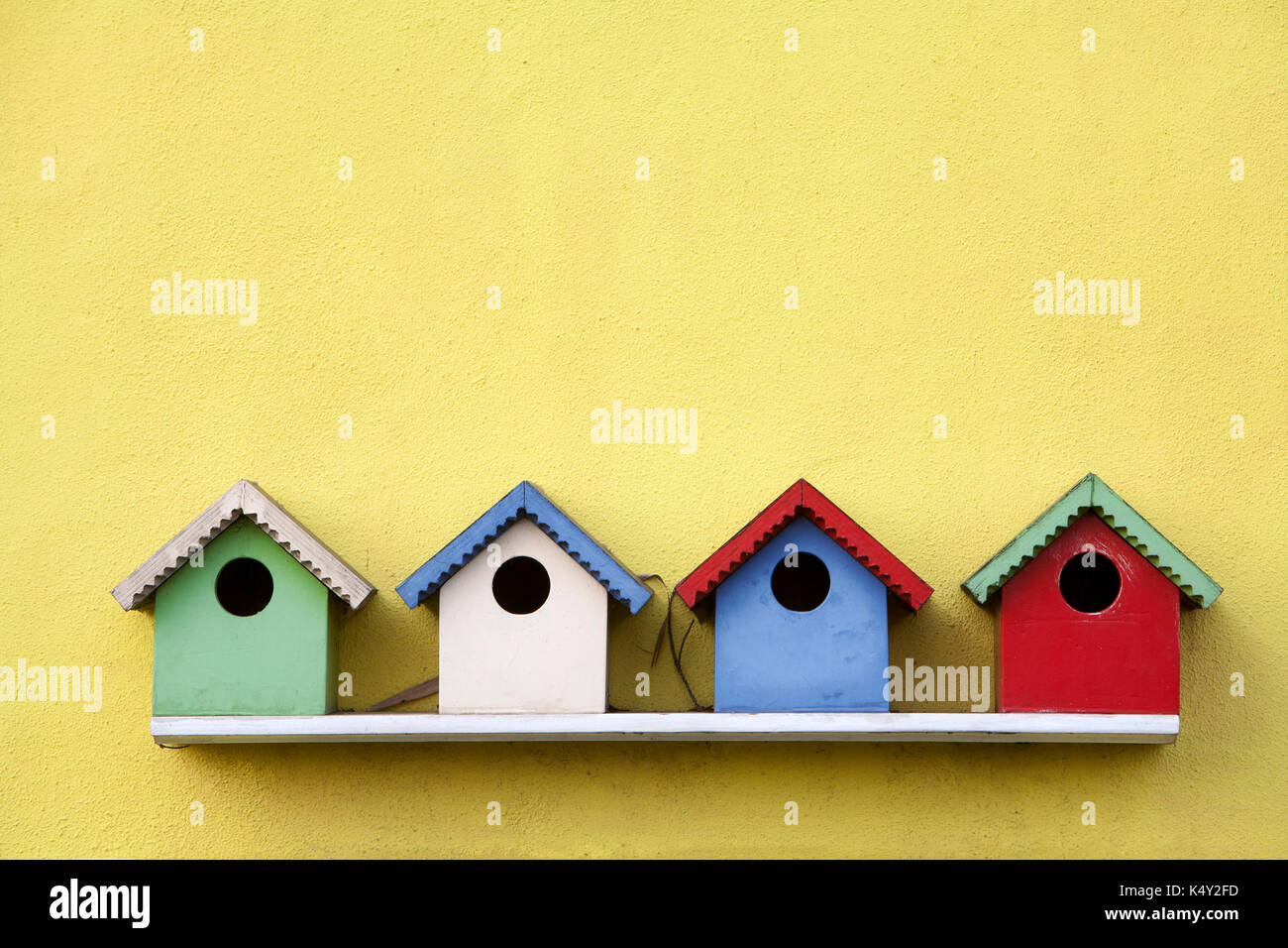 Street of four colorful birdhouses hanging on a yellow wall - Stock Image