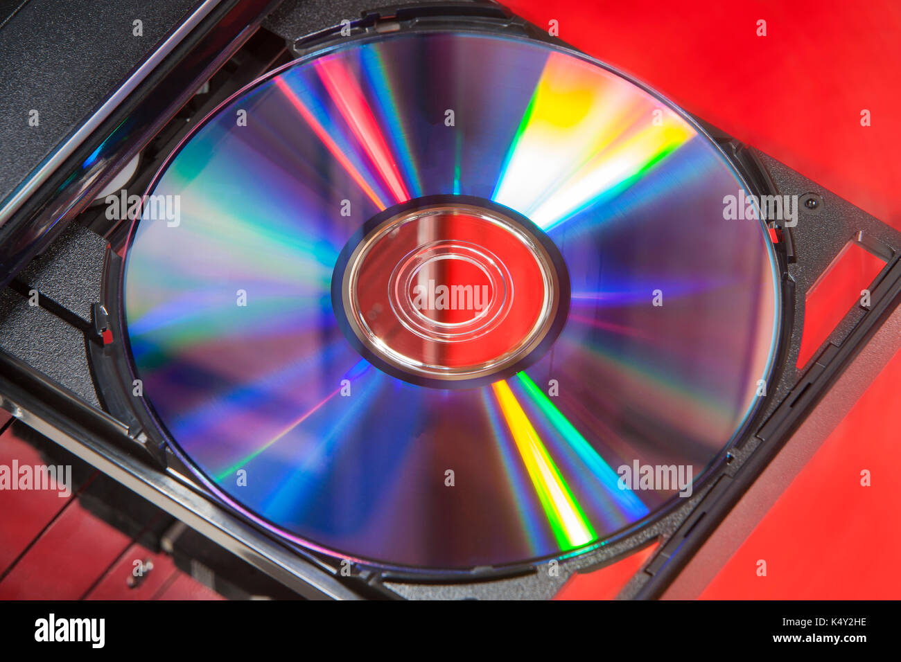 DVD disc in player of a desktop computer with a red background - Stock Image