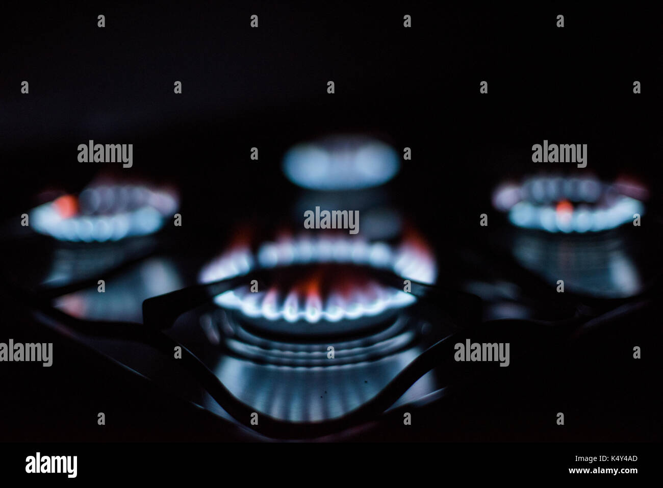 Rings of fire: four lighted gas stove burners. - Stock Image