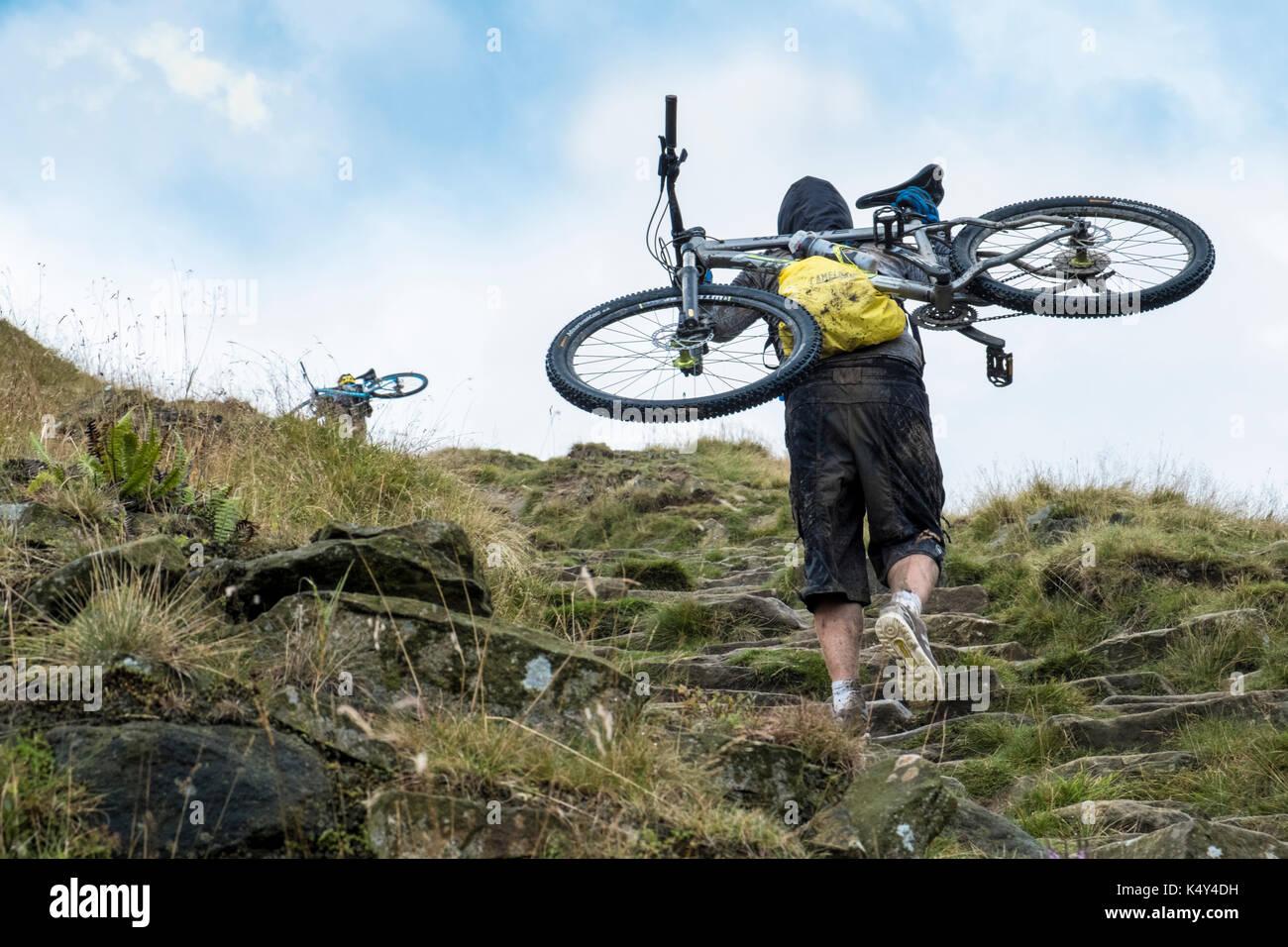 Mountain biker: Cyclist carrying a mountain bike up a hill. Jacob's Ladder, Derbyshire, England, UK - Stock Image