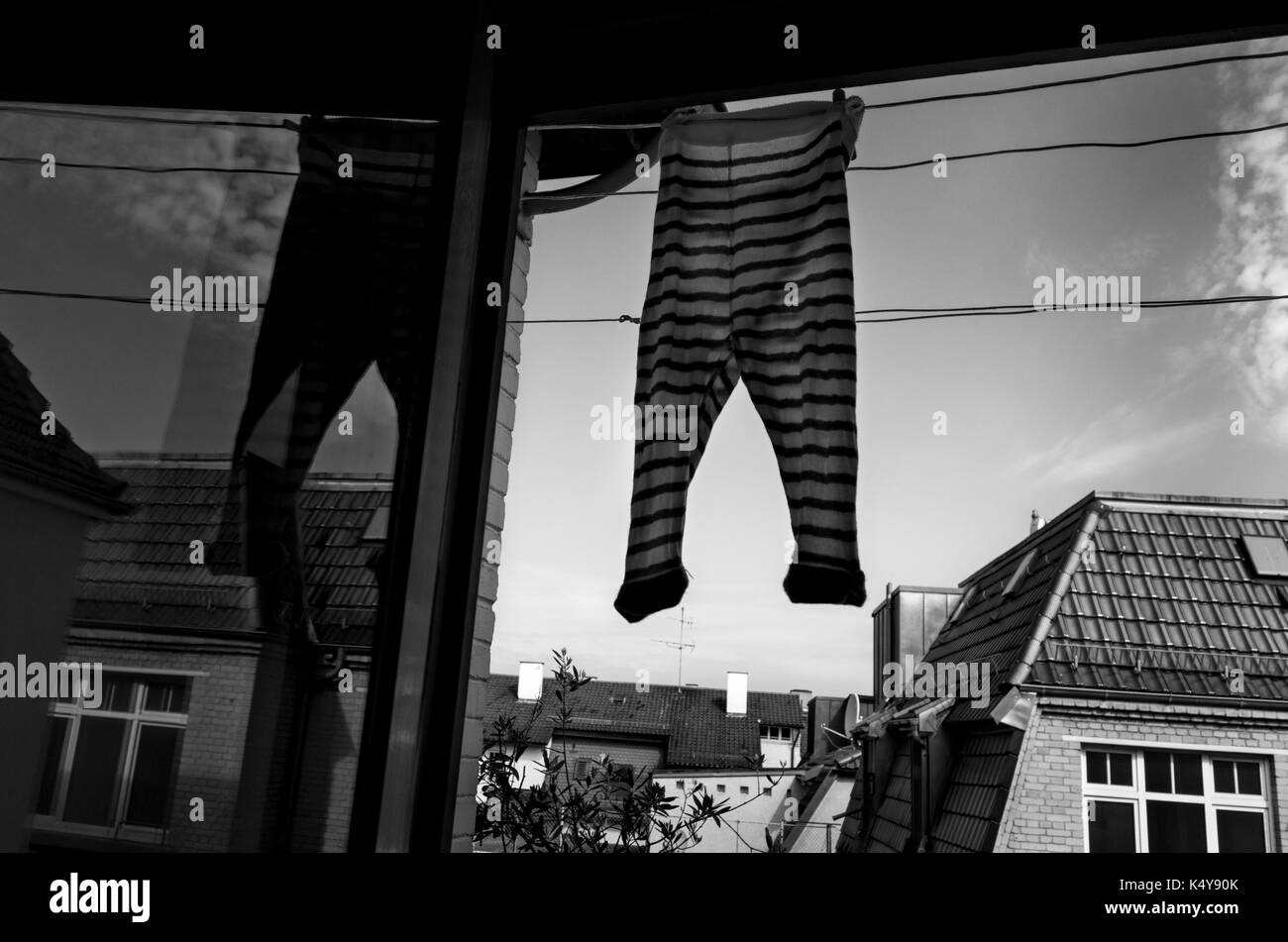 Baby jumpsuit hanging to dry on a balcony. - Stock Image
