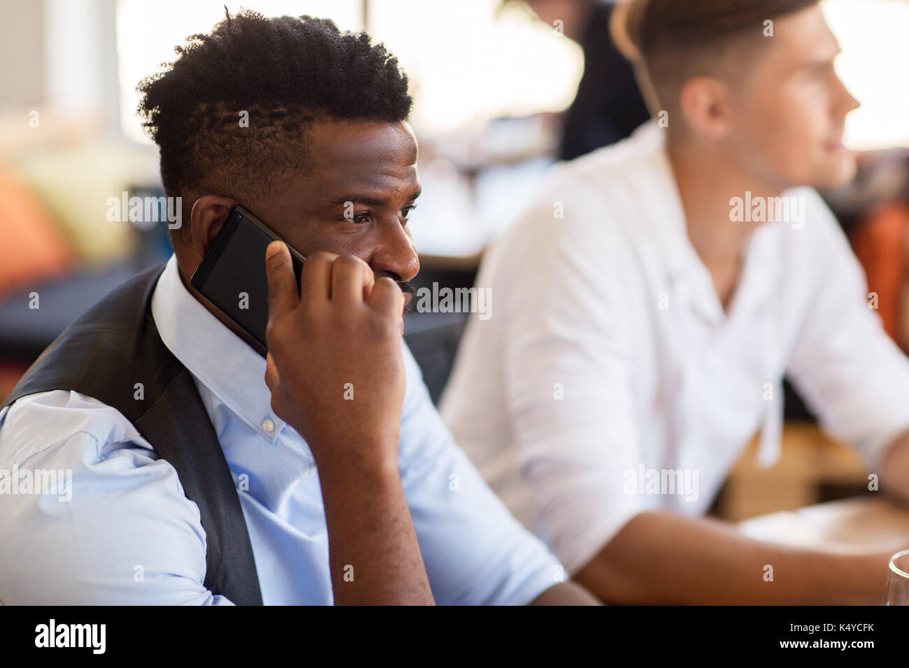 man calling on smartphone at bar or restaurant - Stock Image