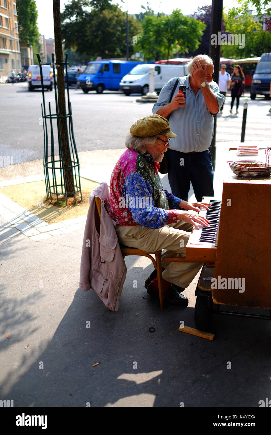 A street musician playing the piano near the antique market stalls in the Marche aux Puces, the flea market, at Porte de Vanves in Paris - Stock Image