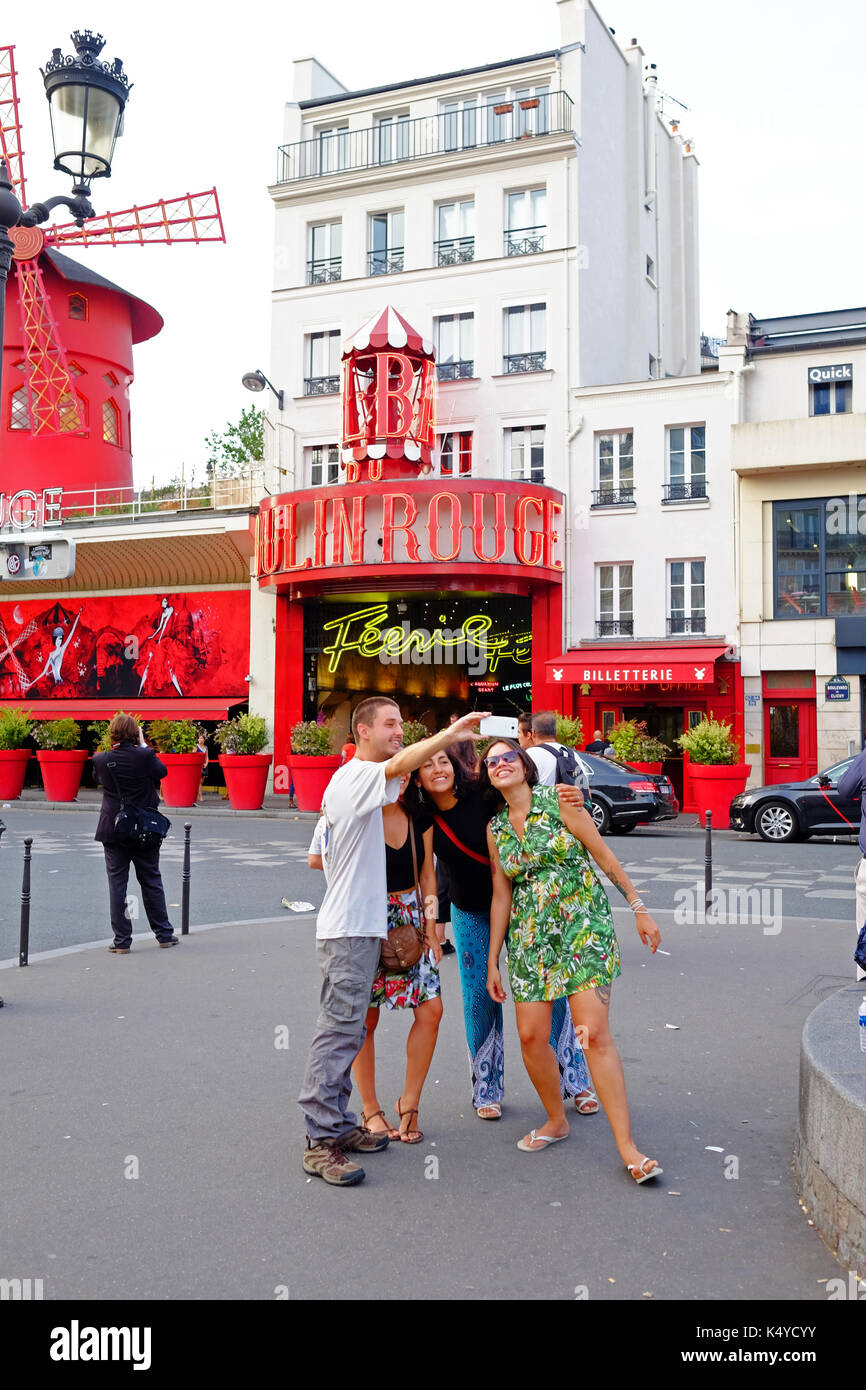 Tourists pose for a selfie group photo n front of the Moulin Rouge cabaret club in Pigalle, close to Montmartre in Paris - Stock Image