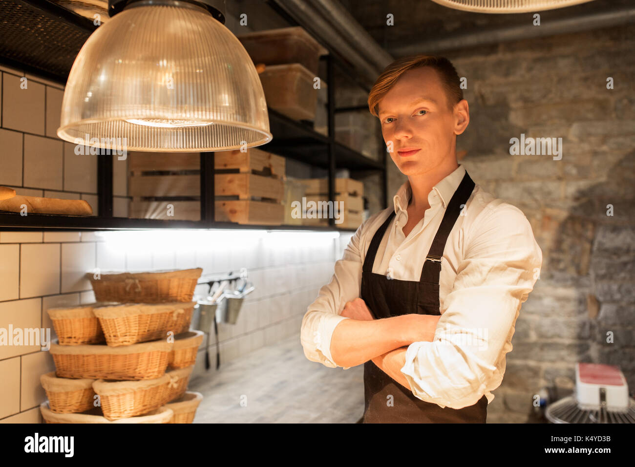chef or baker in apron at bakery kitchen - Stock Image