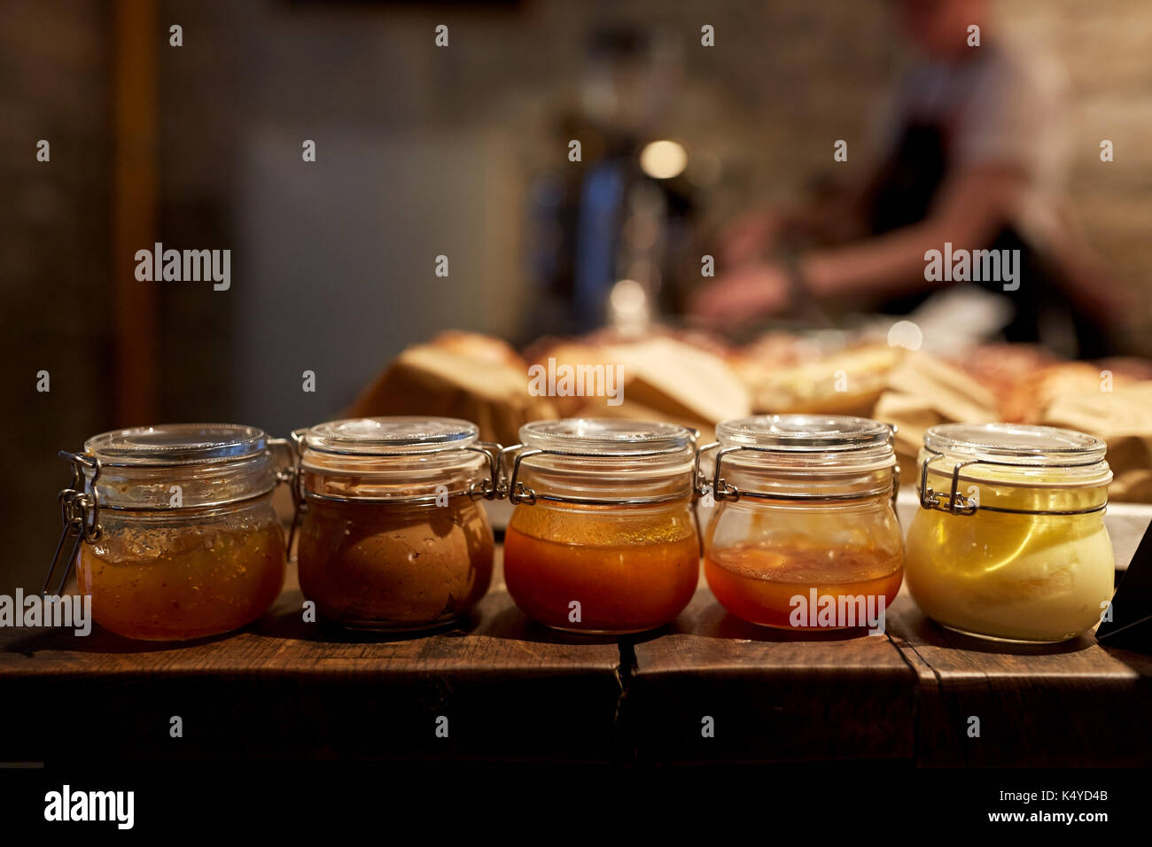 jars with craft jam or sauce at grocery store - Stock Image
