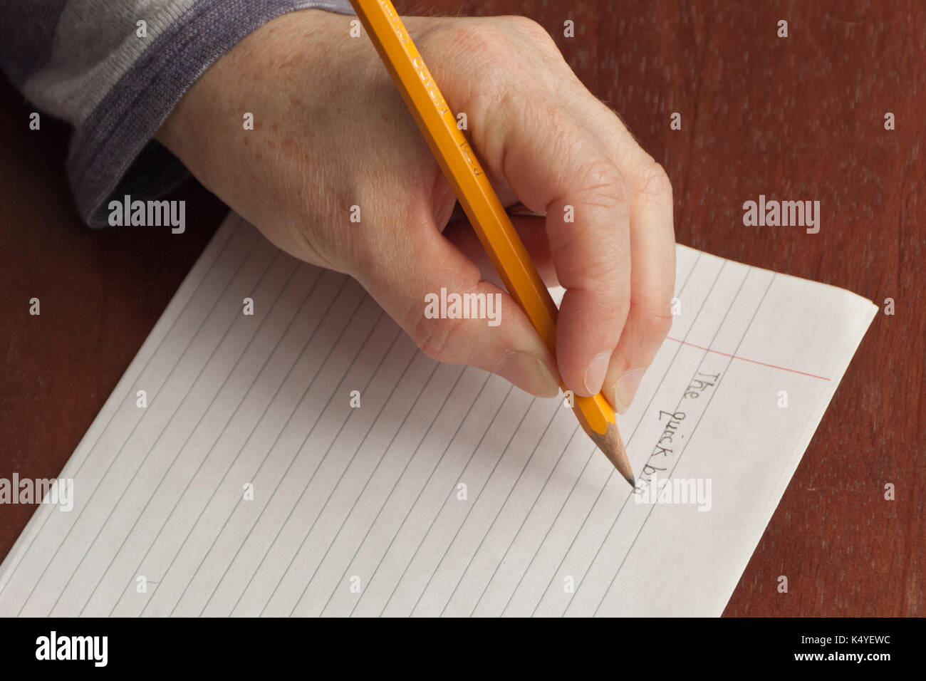 Left hand writing with pencil - Stock Image