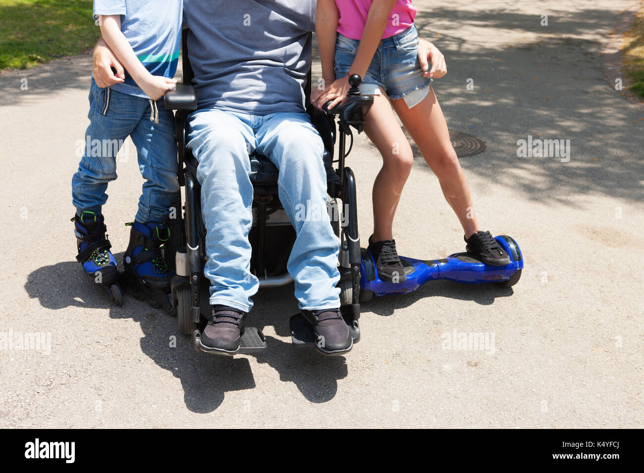 Disabled father on the wheelchair playing with children. - Stock Image