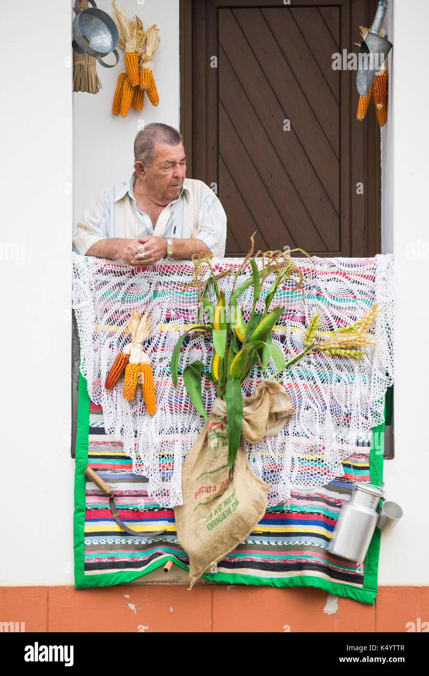 Teror, Gran Canaria, Canary Islands, Spain. 7th Sep, 2017. Every year on the 7/8th Sept, thousands of peregrinos (pilgrims) make their way to the mountain village of Teror on Gran Canaria to pay their respects to the island`s patron saint, nuestra senora del pino. PICTURED: A man watches the street parade from his balcony. Credit: ALAN DAWSON/Alamy Live News - Stock Image