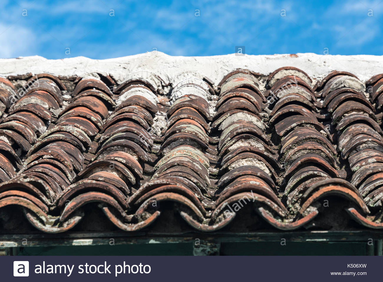 Rows of old clay pantiles laid on a roof, timeworn and blackened they are. - Stock Image