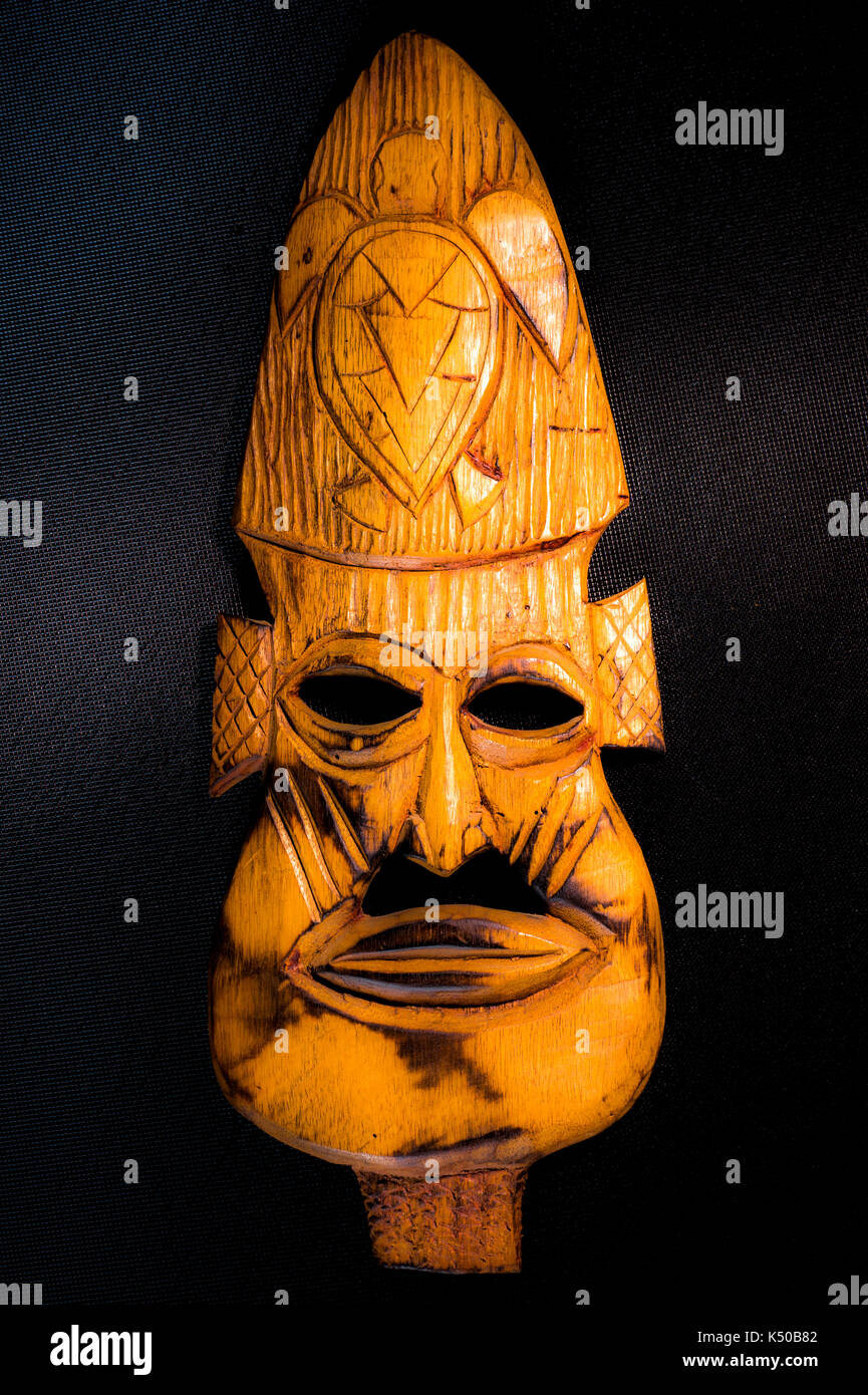 Hand carved, African Caribbean, tribal wood / wooden mask, made by a local man at Turtle Beach holiday resort, Western Tobago, Caribbean, West Indies. - Stock Image