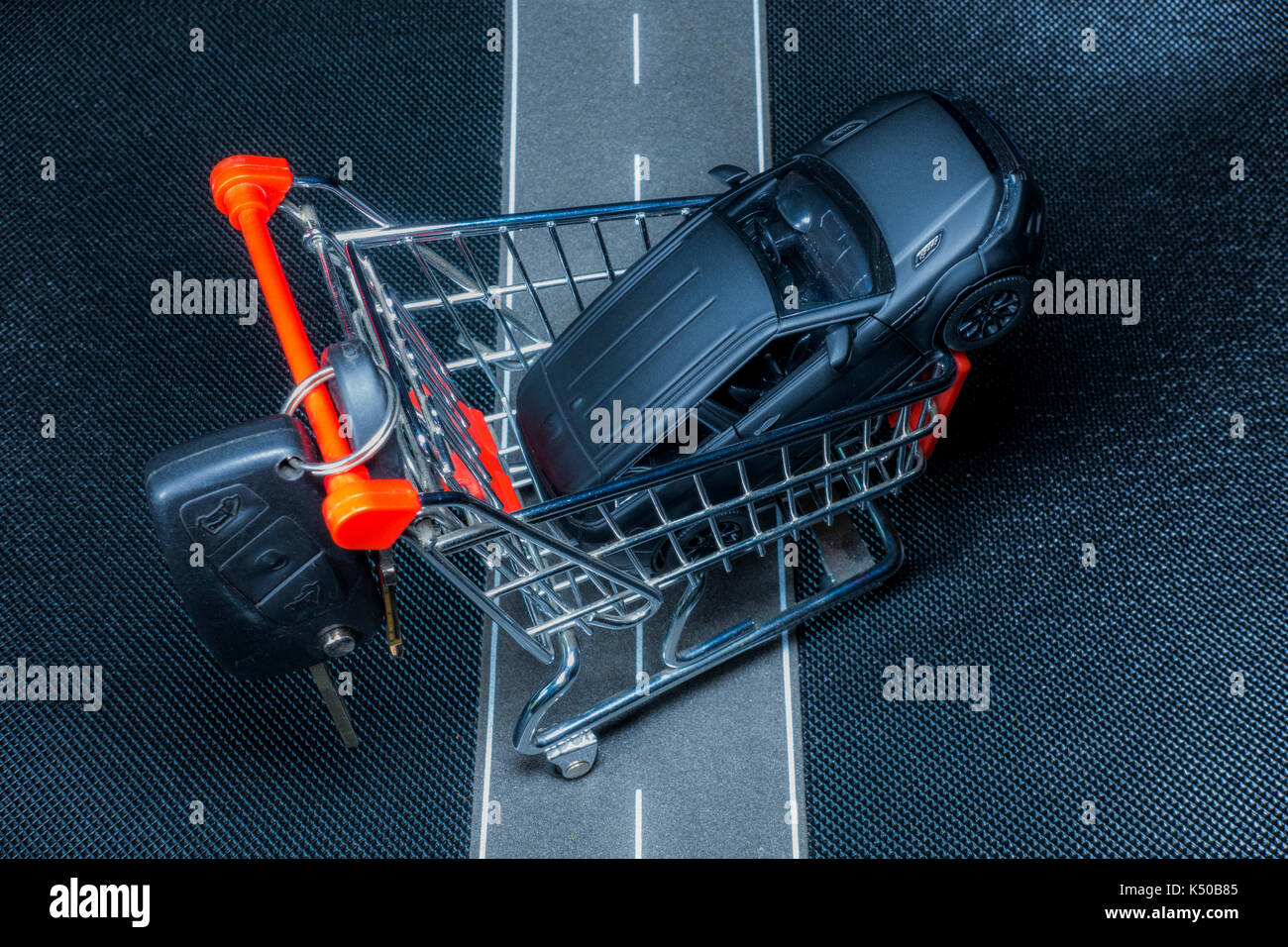 A closeup model shopping trolley holding a black model car on a lifelike road. Real Keys are added to illustrate the business concept of buying a car. - Stock Image