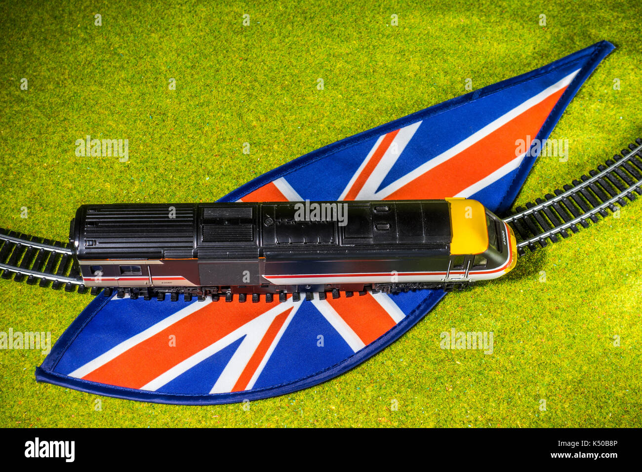 A model train and track on Union Jack colours, surrounded by grass, depicting the general concept of UK train travel. - Stock Image