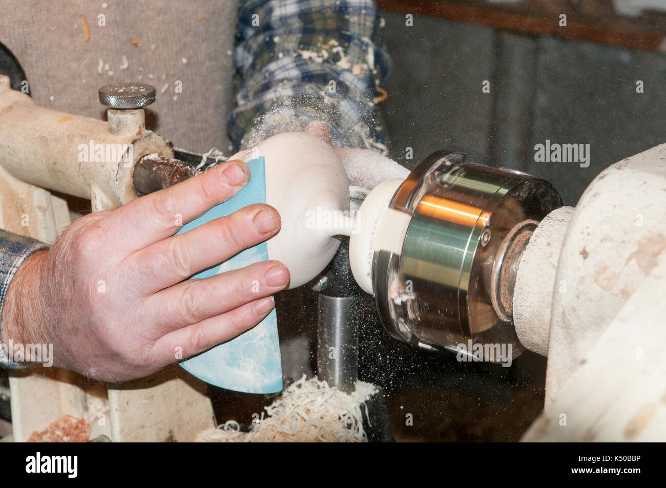 Master grinds on the machine, emery cloth, candlestick - Stock Image