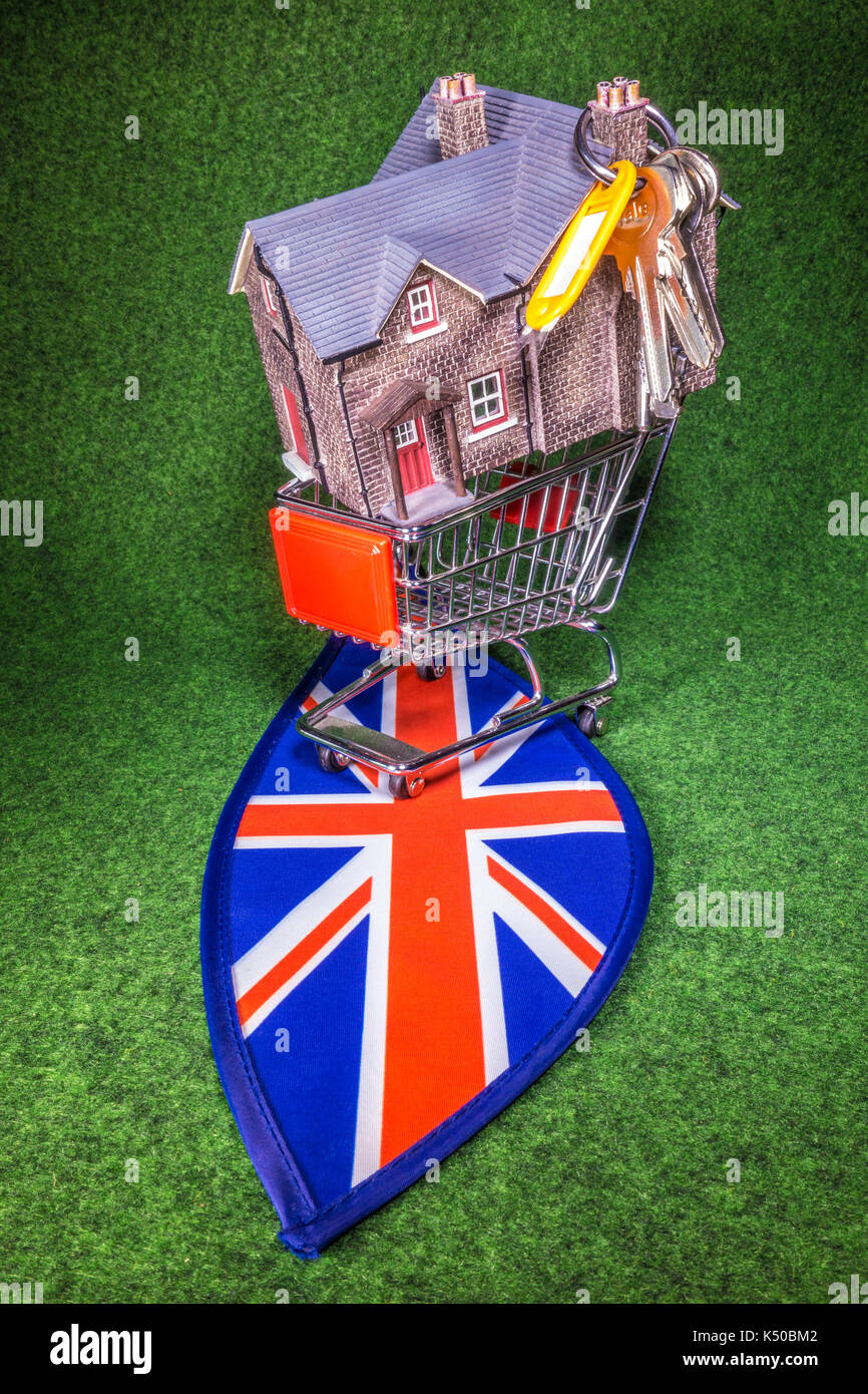 Model house in a model shopping trolley, with house keys, on Union Jack colours. A concept to depict the UK housing market of home buying or renting. - Stock Image