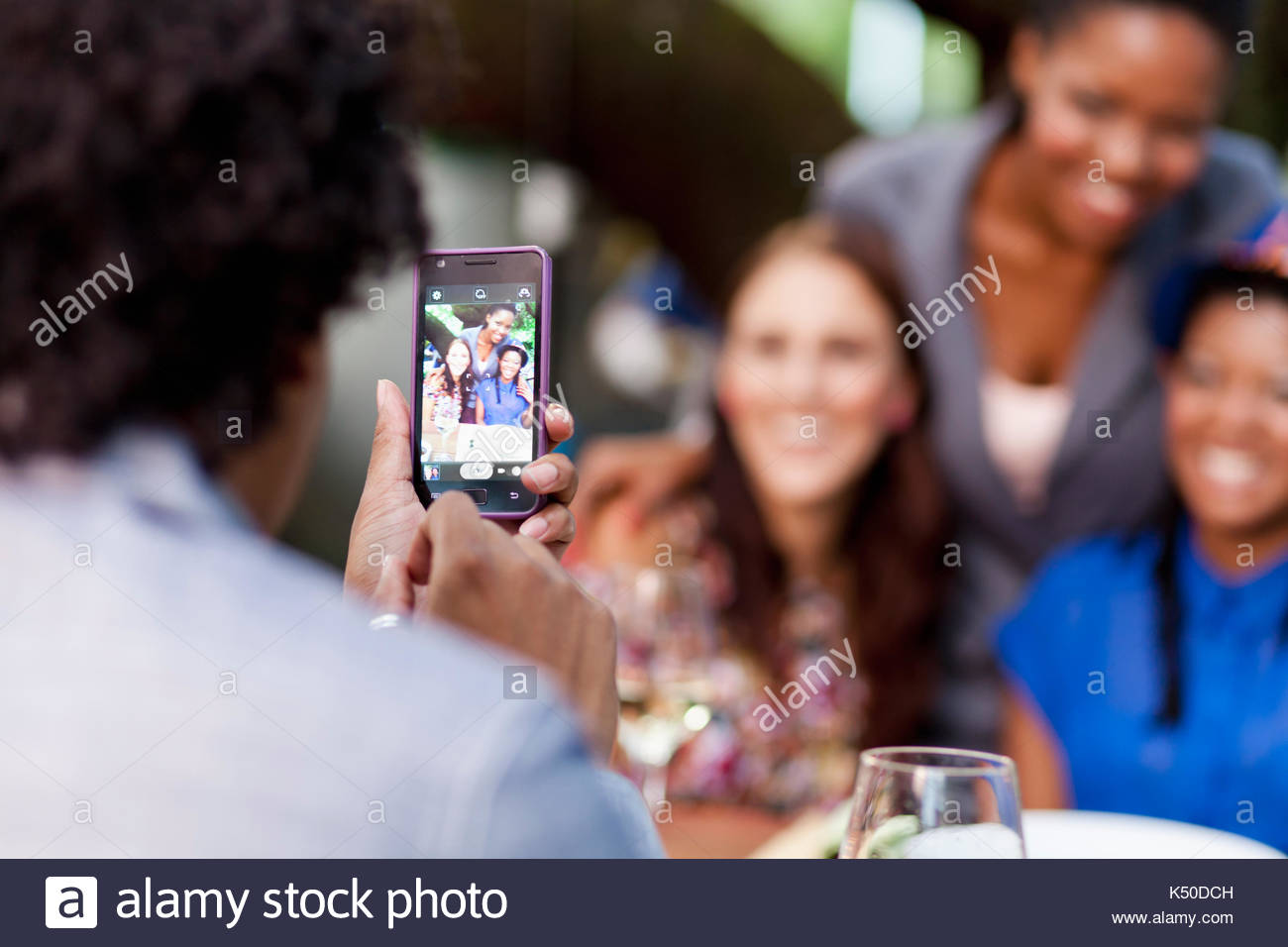 Man taking a photo of three friends with his cellphone - Stock Image