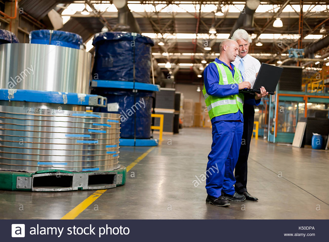 Young white man showing a colleague something on his laptop at a warehouse - Stock Image