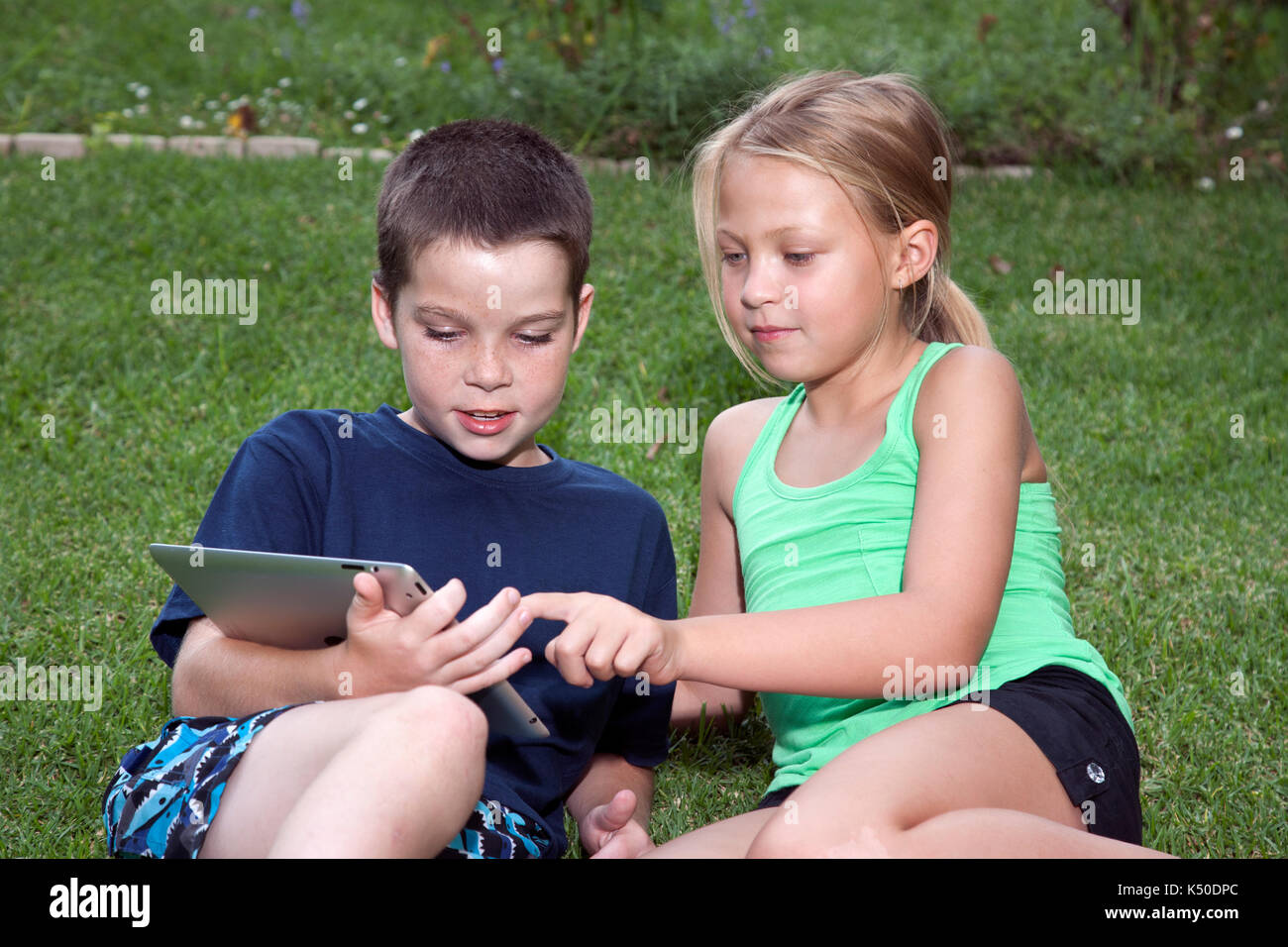 Two kids playing on an iPad - Stock Image